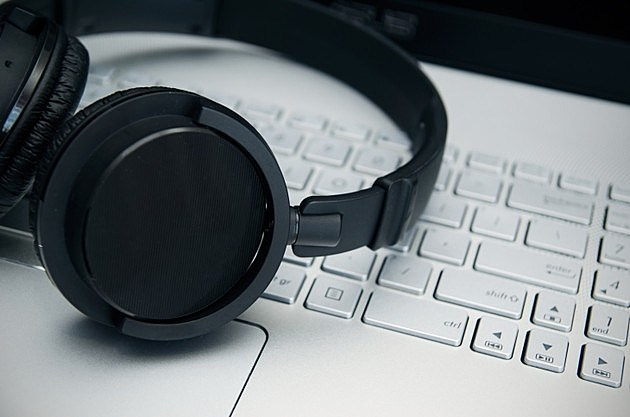 Wireless headphones on laptop keyboard. Music and gaming concept