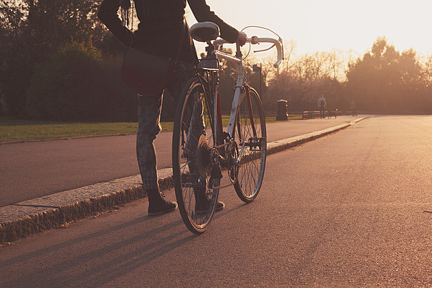 A Young woman is standing with her bicycle in the park at sunset