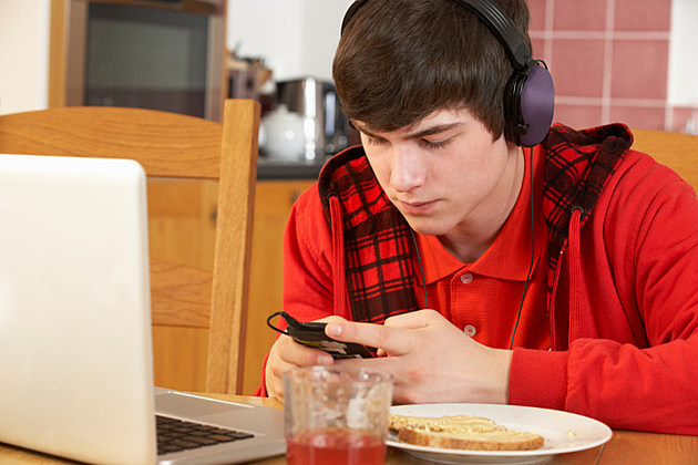 Teenage Boy Using Laptop And Listening To MP3 Player