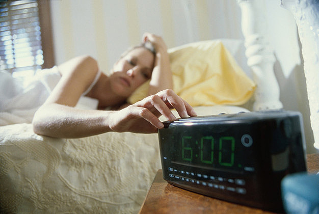 Young woman lying in bed reaching for an alarm clock